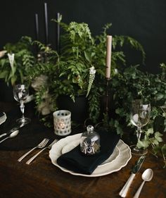 "Set the scene for an elegant gathering with a dark and moody table, like this one by Cassandra Lavalle of coco+kelley. Just add some ""creeping"" foliage for the centerpiece, black candles, napkins, vintage-inspired plates, and a tablecloth."