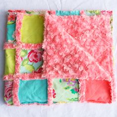 Beautiful floral prints and bright colors come together in this quilt. It has a modern shabby chic look.  It is mainly turquoise, coral, and light green with a gorgeous rose minky on the back.