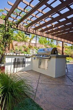A L-shaped outdoor kitchen located under a patio cover for much needed shade. Designed by Revive Landscape Design.