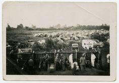 "Motorbikes at the Aranui Speedway, off Rowan Ave and Pages Road. The 'holding pit' in the foreground where bikes and racers waited for their race. Stockcars and midgets also raced, a popular form of entertainment at the time. ""There was only the picture theatre and speedway"". A lot of the early helmets were made out of papier mache. The photograph was taken on Jack's Box Brownie camera. Date: 1950."