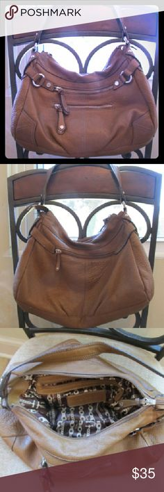 Tignanello genuine leather hobo bag Outside is made from genuine leather. Brown/tan in color. There are two zipper pockets on the front, one on the back, one inside and two pouches inside. There is some pink nail polish drops on the bottom of the bag. Tignanello Bags Hobos