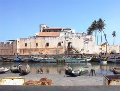 Elmina Castle played a significant part in the Atlantic Slave Trade. Elmina Castle was erected by Portuguese in 1482  in present-day Elmina, Ghana (formerly the Gold Coast). It was the first trading post built on the Gulf of Guinea, so is the oldest European building in existence below the Sahara. First established as a trade settlement, the castle later became one of the most important stops on the route of the Atlantic slave trade.