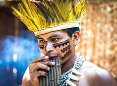 Native Brazilian playing wooden flute by Filipe Frazao