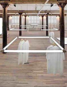 interior de una tienda de ropa, donde la ropa esta colgada de flexos de luz blanca que forman cuadrados, muy original y exclusiva dado que vemos poca ropa.  Alejandro Estevez