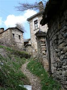A lonely trail climbing up beside the stone walls of typical houses in a northern Albanian village.