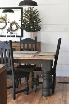 Rustic Farmhouse Christmas Dining Room. Table and Chairs painted black and paired with wood floors.