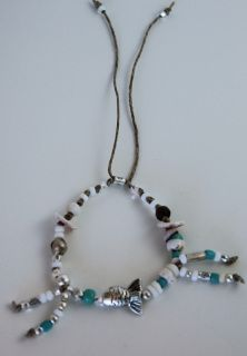 item #B067 The other fish in the sea bracelet is made with a lone silver fish in the center surrounded by a selection of seashells, pukas, glass beads, bone beads, turquoise, antique african beads, and beautiful silver fish charm all beaded on natural cord.