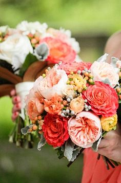 "The bridesmaids will carry small textured clutch bouquet of coral-red ""Free Spirit"" garden roses, peachy-pink ""Juliet"" garden roses, ivory lisianthus with green buds, peach hypericum berries, peach spray roses, coral-red spray roses, and gray dusty miller wrapped in peach satin ribbon"