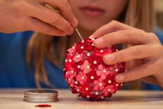 Styrofoam ball, scrapbook embellishing flowers, and straight pins with rounded heads. . .hang with a ribbon -- beautiful!  Might want to paint the ball the color of the flowers before beginning?