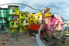 (2 of 2) This is the center square of Santa Marta, a community in the heart of Rio de Janeiro, after a facade make-over by Favela Painting.    Started by Dutch designers Jeroen Koolhas and Dre Urhahn, the Favela Painting projects aim to bring works of art to the slum neighborhoods of Brazil.