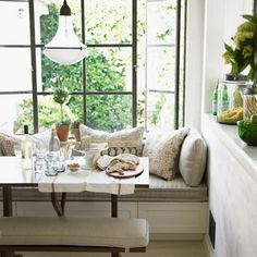 Love everything about this breakfast nook—the window seat piled high with pillows, the wood table with matching bench, the antique-style lantern.