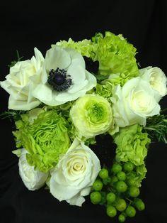 Green hydrangea, garden roses, hypericum, white roses, ranunculas, anemonies, black cosmos and rosemary.