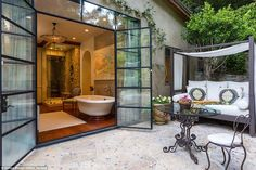 A bathroom in the home, which has both a shower and a separate tub, opens up into an outdo...