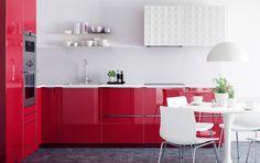 Keittiö, jossa korkeakiiltoisia punaisia ovia ja teräspintainen RUTINERAD-uuni.