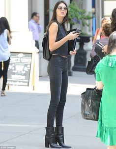 Slim and trim: Kendall Jenner sported a black sleeveless crop top with diamond pattern and...