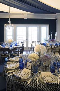 Navy and white tables look crisp and classic with silver-rimmed wine glasses, silver chargers and white candles in glass holders.