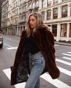 Cozy brown faux fur jacket over black top and blue jeans.