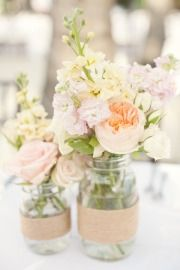 Other tables will feature a trio of mason jars wrapped in natural burlap filled with antique green hydrangeas, pale pink spray roses, ivory lisianthus, pale pink stsock flowers, peach hypericum berries, grey dusty miller, and seeded eucalyptus surrounded by gold mercury glass votives.