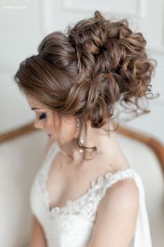 Venician textured curls woven into a high messy bun