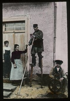 A hand-coloured photographic lantern slide of a Landes postman on stilts delivering a letter to a woman, France. There is another woman standing on the door-step behind and a man seated in front of a spinning wheel in the bottom right hand corner. (2012-0030/04)