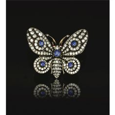 PROPERTY OF A BRITISH NOBLE FAMILY Sapphire, ruby and diamond brooch, Late 19th Century. The butterfly of open work design set en tremblant with old mine diamonds, and highlighted with circular-cut sapphires.