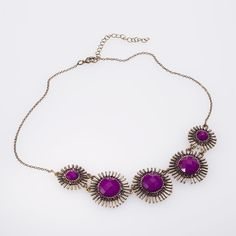 This statement necklace has 5 plum berry faceted beads set in antique gold finished settings that are surrounded by circular rows of spikes. Do not forget to check out the matching earring.