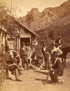 Bakery at Manitou Springs - 1877    This photo of a bakery along Ute Pass near Manitou, Colorado is believed to have belonged to William Iles. William Iles is believed to be the bearded man in front of the door. His daughter Annie Iles is believed to be the girl in the doorway. The rest of the people are unknown. The rock formation Tim Bunker's Pulpit is in the background.