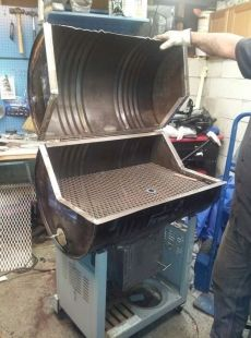 Homemade charcoal grill and smoker constructed from a steel drum, angle iron, wire mesh, and a wheeled stand.