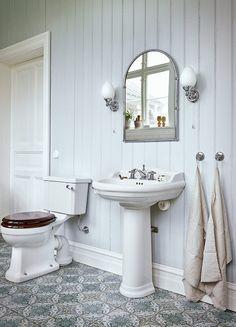 Högt i tak och väl genomtänkta färger och detaljer. Spontad panel och gjutjärnsbadkar sätter stilen i detta ljuvliga romantiska badrum.