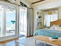 Masterful Beach Bedroom: Whitewashed furniture, like the bedside table and bench at the foot of the bed add soothing casualness to this Seaside, Florida master bedroom. Vaulted, wood-paneled ceilings lend a sense of drama to the room.