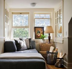Notice the woven baskets that double up as a bedside table for a small guest room. Lovely double hung windows, earthy colours and wall paneling add a lovely ambiance to the room.
