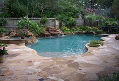 This is a beautiful free from pool with a tropical feel. There is a lovely overhanging waterfall flanked by a low rock wall on either side. To the left is a raised spa with its own waterfall and a stacked stone spill into the pool. The decking around the pool is all flagstone and there…