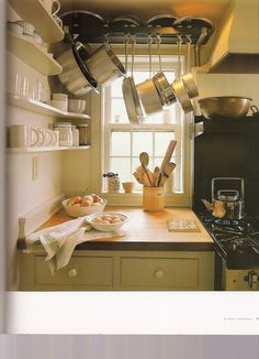 In order not to block a window beside stove, places open storage on wall and hung pots and lids above, but not blocking window. Clever.