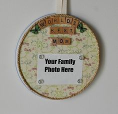 """Personalized Mother's Day Frame and Magnet Board. This is a 10"""" in diameter tin magnetic photo frame - covered in a neutral tan background with lavender, blue, and green flowers. With Mother's Day being around the corner, I made """"World's Best Mom"""" magnets using Scrabble Tiles. I added 2 butterfly button magnets as well. Then underneath that, you add your own 4""""X6"""" size family photo. I have 4 glitter glass magnets that I am including that will hold your family photo to the board. What I…"""