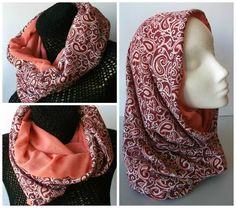 Cuello tubular realizado en tela de punto de algodón, con estampado en tonos rojo, blanco y rosa, combinado con una tela interior de gasa de color salmón.