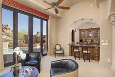 The formal living room is the ideal reception area; complete with a dual-sided fireplace, wet bar with a wine cooler, & doors that lead out to the pool and patio area. #SupremeAuction #LuxuryAuction #Scottsdale #Phoenix #Arizona #ScottsdaleRealEstate #SonoranDesert #ArizonaRealEstate #Troon #TroonVillage #Auction #Artesano