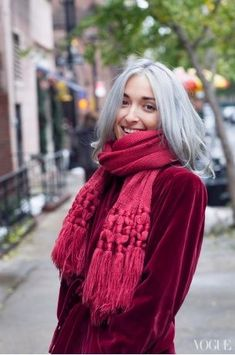 Beautiful tranisiton to grey hair.  The grey hair suits her and looks lovely against the ruby red colour of her coat and scarf.