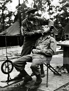 circa 1943, A foot operated drill in operation as a US soldier sits in the dentist's chair, the dentist working a makeshift camp in eastern Australia, where the Americans were on manouvres