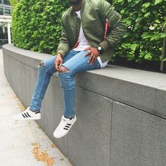 Opt for an army green bomber jacket and baby blue ripped slim jeans to create a great weekend-ready look. This outfit is complemented perfectly with white low top sneakers. Shop this look on Lookastic: https://lookastic.com/men/looks/bomber-jacket-crew-neck-t-shirt-skinny-jeans/19640 — Olive Bomber Jacket — White Crew-neck T-shirt — Black Leather Watch — Light Blue Ripped Skinny Jeans — White Low Top Sneakers