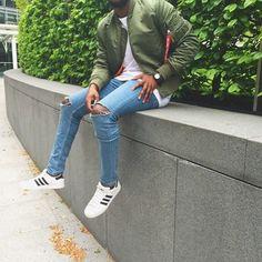 Acheter la tenue sur Lookastic: https://lookastic.fr/mode-homme/tenues/blouson-aviateur-t-shirt-a-col-rond-jean-skinny/19640   — Blouson aviateur olive  — T-shirt à col rond blanc  — Montre en cuir noir  — Jean skinny déchiré bleu clair  — Baskets basses blanches