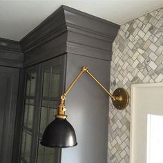 Kitchen details from our 1928 Dutch colonial. IKEA hack kitchen cabinets in lidingo grey. Custom crown molding with paint match by Sherwin Williams. AKDO tumbled marbled herringbone backsplash with grey grout. Schoolhouse electric Princeton senior sconce in natural brass.