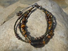 BR52. Triple-stranded bracelet with Japanese glass and brass beads with smoky quartz centrepiece. Smoky quartz clasp detail. $25. https://www.facebook.com/photo.php?fbid=218881251607211&set=a.141503356011668.29288.141493752679295&type=3&theater