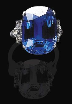 A SAPPHIRE AND DIAMOND RING, BY BULGARI   Set with a modified cushion-cut sapphire weighing approximately 19.53 carats, flanked by bullet and baguette-cut diamonds, mounted in platinum, in a leather box  Signed Bulgari