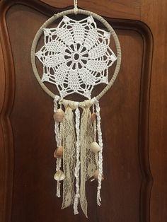 Filtro de sonhos em crochê com acabamento em camurça, adornado com rendas e conchas.