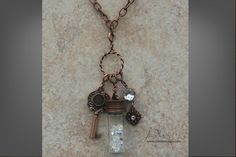 """Copper 36"""" Imagine Necklace, Twist Connector, Large Key, Keepsake Glass Bottle, crystal inserts for the bottle, Crystal and Flower Dangle. These items are also available in Antique Silver and Antique Gold. Total cost for pieces shown in the picture $132. www.jbloomdesigns.com"""