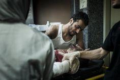 Un blessé est réconforté dans un hôpital de fortune.