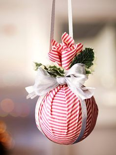 """No Fuss Kissing Ball.  Wrap a 4"""" styrofoam ball in a 14"""" fabric square; secure with a rubber band. Thread the end of 1 1/2 yards of ribbon down through the band, around the ball, and up through the band's other side so ribbon ends match up (knot them to hang the ball).  Wrap 14"""" of ribbon around the ball's other side (crossing first ribbon, as shown); tuck ends into band. Hide band with s shimmery bow and festive sprigs."""