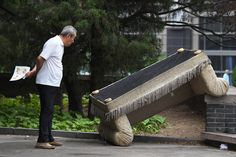 A man looks at a discarded sofa on a street in Beijing on May 30, 2017.
