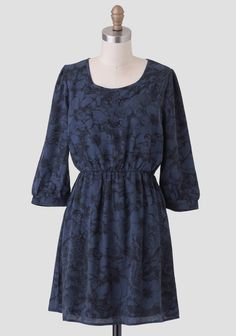 This deep navy blue dress features a refined black floral print allover with a back cutout and three-quarter sleeves for a chic silhouette. Finished with an elastic waistline for the perfect fit,...