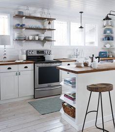 The owner of this Alberta farmhouse skipped curtains to lighten up the room's look and maximize views of the scenic property. Minimalist iron-and-glass pendant fixtures cast plenty of light on the work spaces without blocking sight lines, while wooden shelves, countertops, and stool seats add warmth.